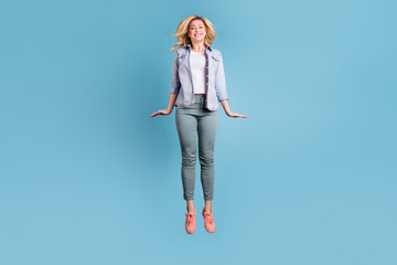Full body photo of attractive pretty lady jumping with beaming toothy smile isolated over blue background