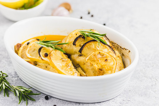 Lemon rosemary chicken breasts in a baking dish. Selective focus, space for text.