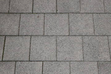 Abstract background with paving slabs on the gray sidewalk, copy space