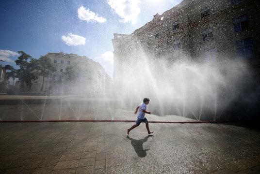 A child runs under water sprinklers during a heat wave in Vienna