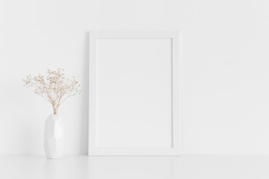White frame mockup with a gypsophila in a vase on a white table.Portrait orientation.