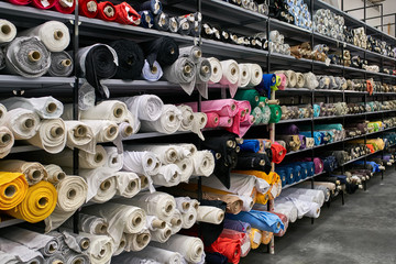 Stores à enrouleur Tissu Fabric warehouse with many multicolored textile rolls