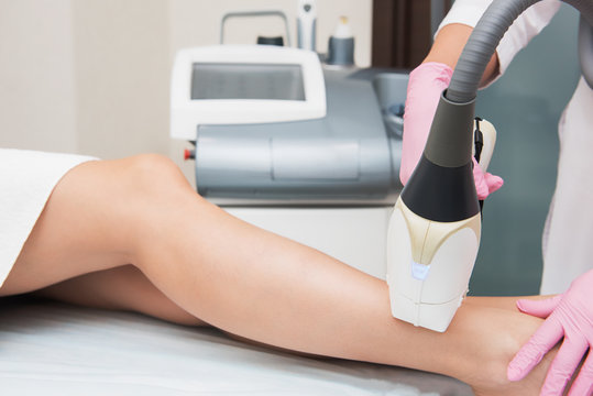 Closeup photo of woman getting laser hair removal procedure on her legs in modern clinic. Cosmetology and SPA concept