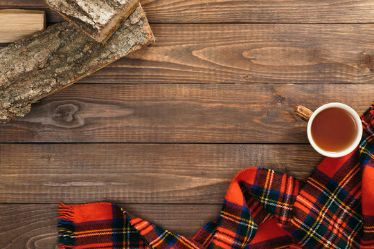 Scandinavian hygge style autumn flatlay composition. Frame of fashion feminine red scarf, cup of tea, firewood on wooden background. Flat lay, top view, copy space. Cozy home office desk table concept