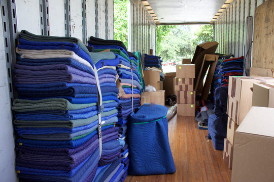 Moving and storage trailer with strapped moving blankets and packed boxes on floor