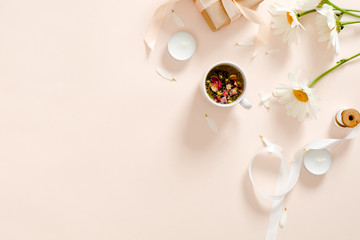Herbal tea, candles, ribbon, gift box, chamomile flower on pastel pink background. Minimal flat lay...