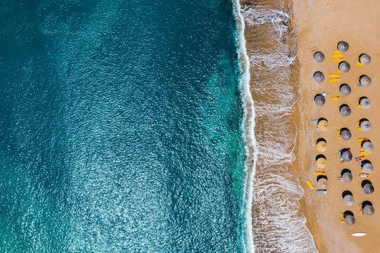 Aerial view of sandy coastline with crystal sea water