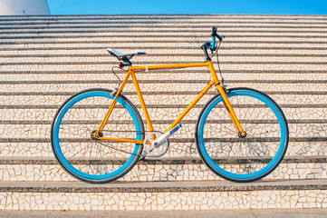 Old yellow fixed gear bicycle on a stairs