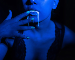 A thick white liquid flows down the lips of a young European girl. Dripping down. Ultraviolet, blue light. Close-up portrait. Spit out.