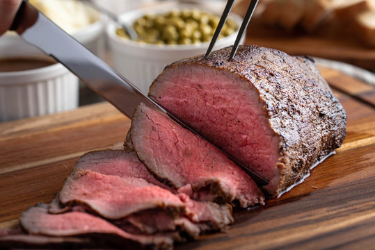 slicing eye of round roasted beef with knife