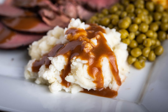 mashed potato serving with gravy sauce on roasted beef platter
