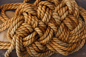 Ropes jute tackle on brown wooden background texture