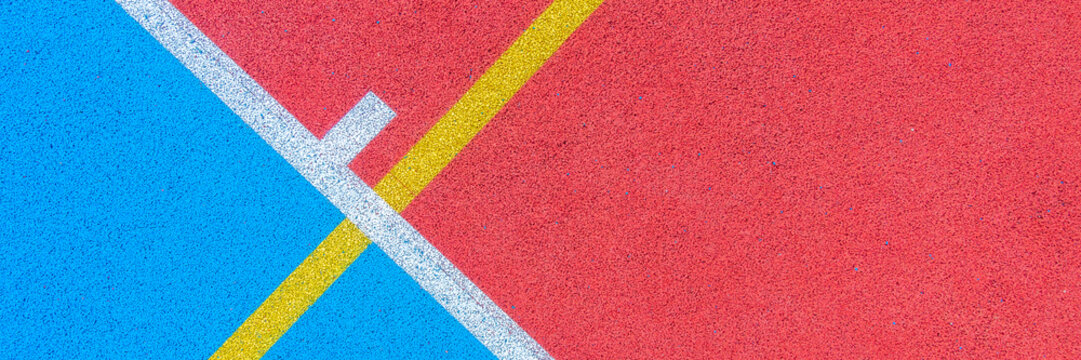 Colorful sports court background. Top view to red and blue field rubber ground with white and yellow lines outdoors