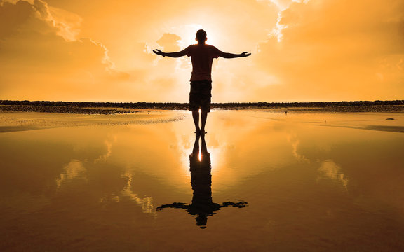 Silhouette of Man Raising His Hands or Open arms when sun rising up
