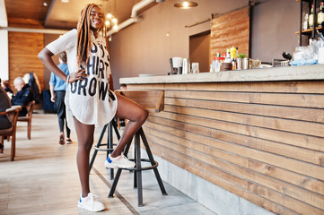 Beautiful african woman in stylish casual clothes posing near bar counter.