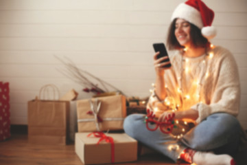 Blurred image of stylish happy girl in santa hat looking at phone screen in festive christmas lights on background o presents and gifts in modern room. Space for text. Happy Holidays