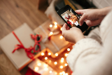 Hands holding phone and taking photo of christmas gift boxes, santa hat, illumination lights on wooden background in dark room. Stylish hipster girl in sweater making christmas flat lay photo