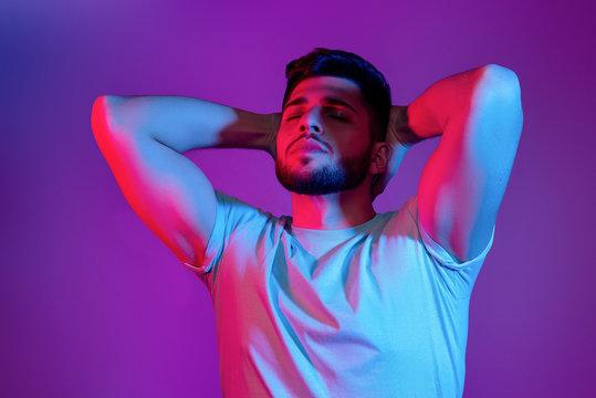 handsome bearded man in neon light posing