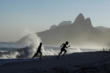 Children run from waves during sunset at Ipanema beach in Rio de Janeiro