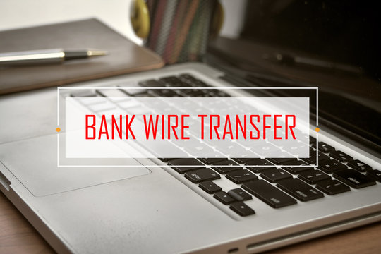 Notebook and Laptop with text BANK WIRE TRANSFER