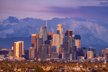 Downtown Los Angeles skyline with snow capped mountains behind at sunset Wall mural