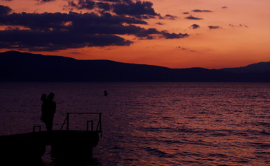 People enjoy the sunset on the coast of Ohrid lake
