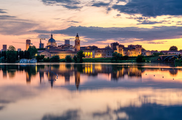 Wall Murals Old building View of the city of Mantua at sunset reflected on the Middle Lake on the Mincio River