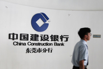 Employee walks past the logo of China Construction Bank at the bank's Dongguan branch office in Guangdong