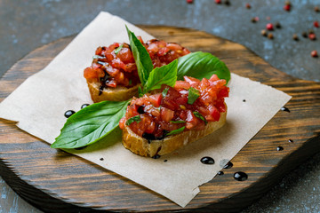 bruschetta with tomatoes and basyl on board on blue concrete table