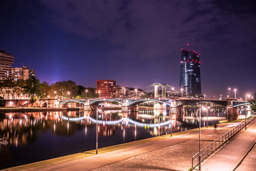 Wall Mural - City of Frankfurt am Main in Germany seen at night with lights, river, buildings and bridge.