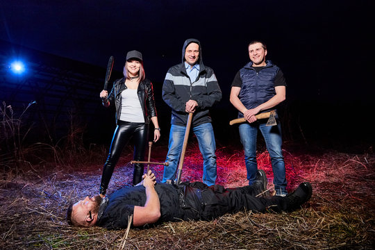 Three bandits near dead man in the field at night. Photoshoot about life of gungsters in Russia