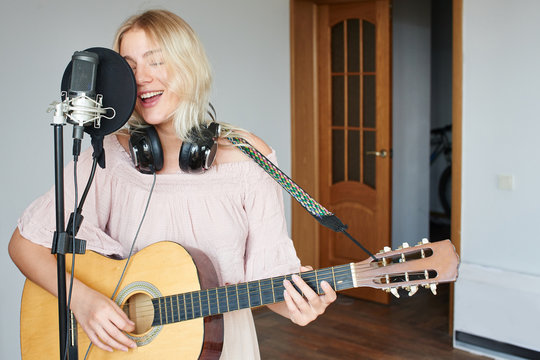 Beautiful blonde singer girl in headphones with a guitar in home recording studio sings a song into a microphone