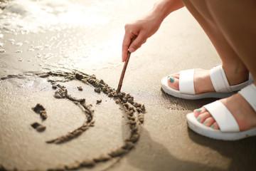 砂浜に絵を描く女性