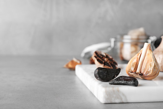 Marble board with black garlic on grey table. Space for text
