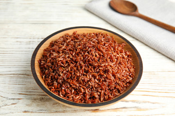 Bowl with delicious cooked brown rice on white wooden table
