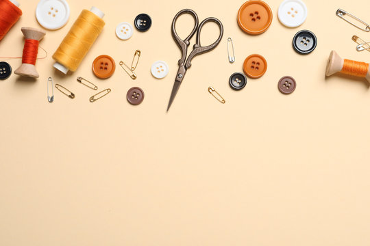 Flat lay composition with scissors and other sewing accessories on light yellow background, space for text
