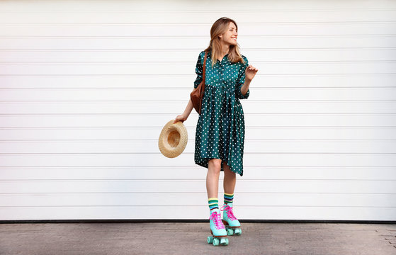 Happy stylish young woman with vintage roller skates, hat and backpack near white garage door on street