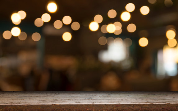 Empty wood table top on blur light gold bokeh of cafe restaurant in dark background