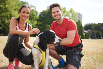 Smiling couple and dog after workout on the fresh air