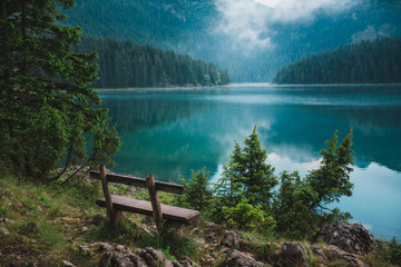 Zelfklevend Fotobehang Groen blauw Peacefull landscape with lake, reflection, mountains and forest in cloudle foggy atmosphere. Durmitor national park in Montenegro, lake Crno