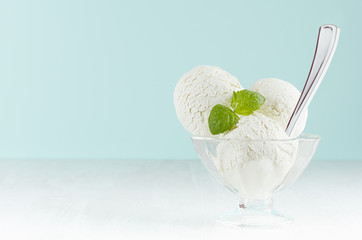 Homemade creamy ice cream scoops in transparent glass ice-cream bowl with green mint, silver spoon in modern blue interior on white wood board.