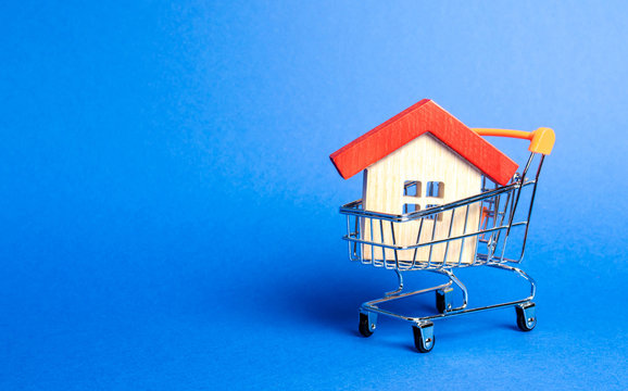 Wooden house in a Supermarket trading cart. The concept of buying a house or apartment. Affordable housing. Profitable and cheap loans for real estate. Buying a home. Mortgage and loan. Place for text