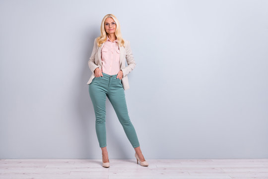 Full length body size view portrait of her she nice attractive pretty charming stylish content cheerful cheery gray-haired lady holding hands in pockets over light white gray background