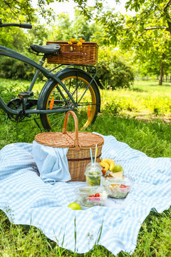 Bicycle and wicker basket with tasty food and drink for romantic picnic in park