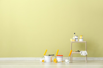 Paints with supplies near wall in room