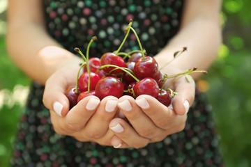 Fototapeten Kirschblüte Woman with handful of ripe cherry outdoors, closeup