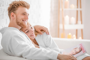 Wall Mural - Happy young couple in bathrobes sitting on sofa at home