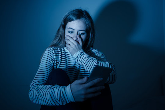 Depressed teenager girl on mobile phone victim of cyberbullying feeling sad, unhappy and lonely