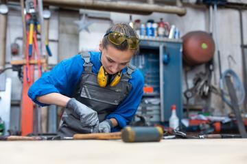 Woman metalworker marking piece of steel