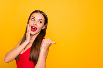 Photo of excited lady bright look indicating fingers empty space advising unbelievable sale discount wear red swimming suit isolated yellow background Wall mural